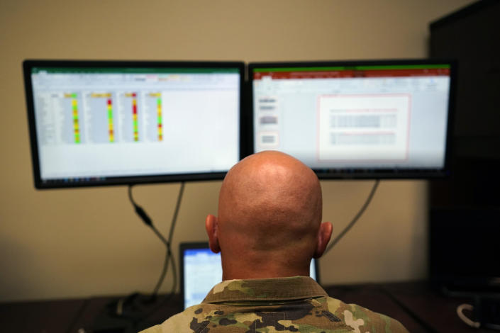 Capt. Michael Switzer sits at his desk before he goes to sleep in his office at Camp Beauregard in Pineville, La., Friday, July 30, 2021. (AP Photo/Gerald Herbert)