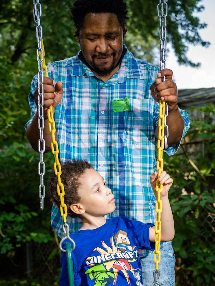 Clareon Williams plays with his father in the backyard of their home in Marham, Ill., on Aug. 10.