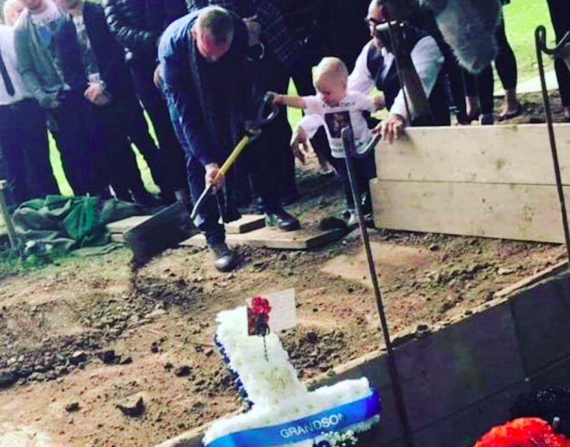 Toddler Carter Bagshaw pours soil over the grave of his father, Lewis Bagshaw (Picture: Jordan Kissack/Facebook)