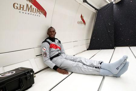 Retired sprinter Usain Bolt poses next to the logo of Mumm Grand Cordon Stellar champagne inside a specially modified Airbus Zero-G plane before a zero gravity conditions flight above Reims, France, September 12, 2018. REUTERS/Benoit Tessier
