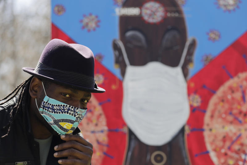In this Tuesday, April 21, 2020 photo, Obi Uwakwe poses with his painting in Chicago. Uwakwe is an artist/photographer and submitted his art work to the the Illinois State Museum, which is documenting what daily life is like for Illinois families during the coronavirus pandemic. (AP Photo/Nam Y. Huh)