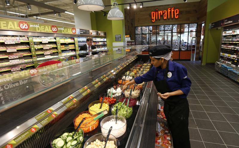 A Tesco employee prepares the salad bar outside the Giraffe restaurant at a Tesco Extra supermarket in Watford, north of London August 8, 2013. REUTERS/Suzanne Plunkett