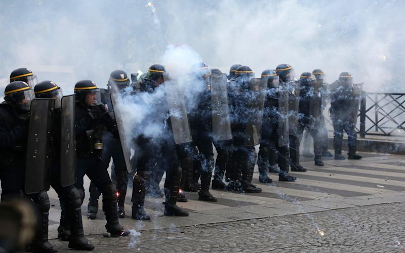 Riot police officers take position as they face youths during the May Day demonstration - Credit: AP