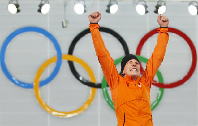 Ireen Wust of the Netherlands celebrates winning gold during the flower ceremony after winning gold in the women's 3,000-meter speedskating race at the Adler Arena Skating Center during the 2014 Winter Olympics, Sunday, Feb. 9, 2014, in Sochi, Russia
