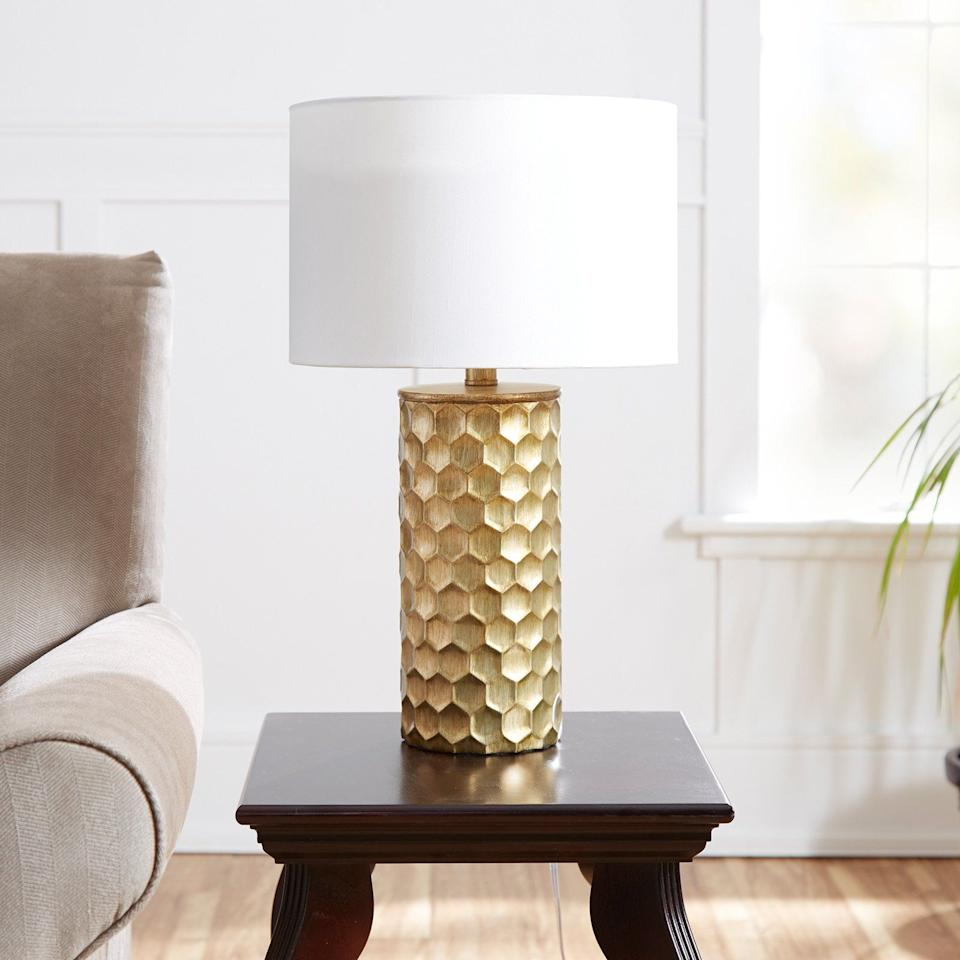 """It just might be the bee's knees — this lamp has a gold geometric base, with the hexagons looking like a hive pattern. This lamp features an ivory shade that's supposed to light up a room, giving off ambient lighting. The lamp comes with a CFL bulb. <a href=""""https://fave.co/35EVS1K"""" target=""""_blank"""" rel=""""noopener noreferrer"""">Find it for $40 at Walmart</a>."""