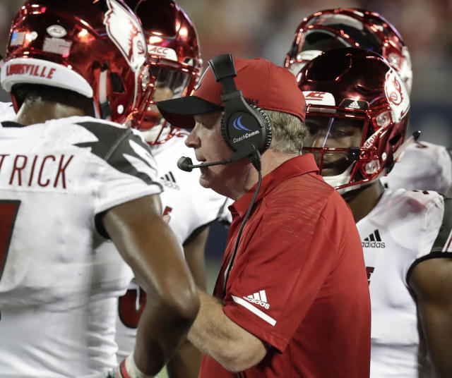 Louisville coach Bobby Petrino talks to his players during a timeout in the first half of an NCAA college football game against Alabama, Saturday, Sept. 1, 2018, in Orlando, Fla. (AP Photo/John Raoux)