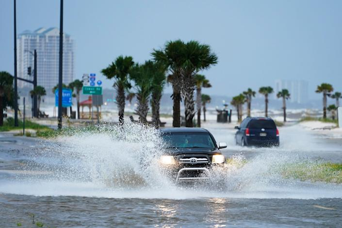 Cars drive through flood waters along route 90 as outer bands of Hurricane Ida arrive Sunday, Aug. 29, 2021, in Gulfport, Miss.