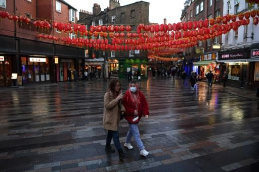 A visitor wears a face mask as she walks through London's Chinatown district