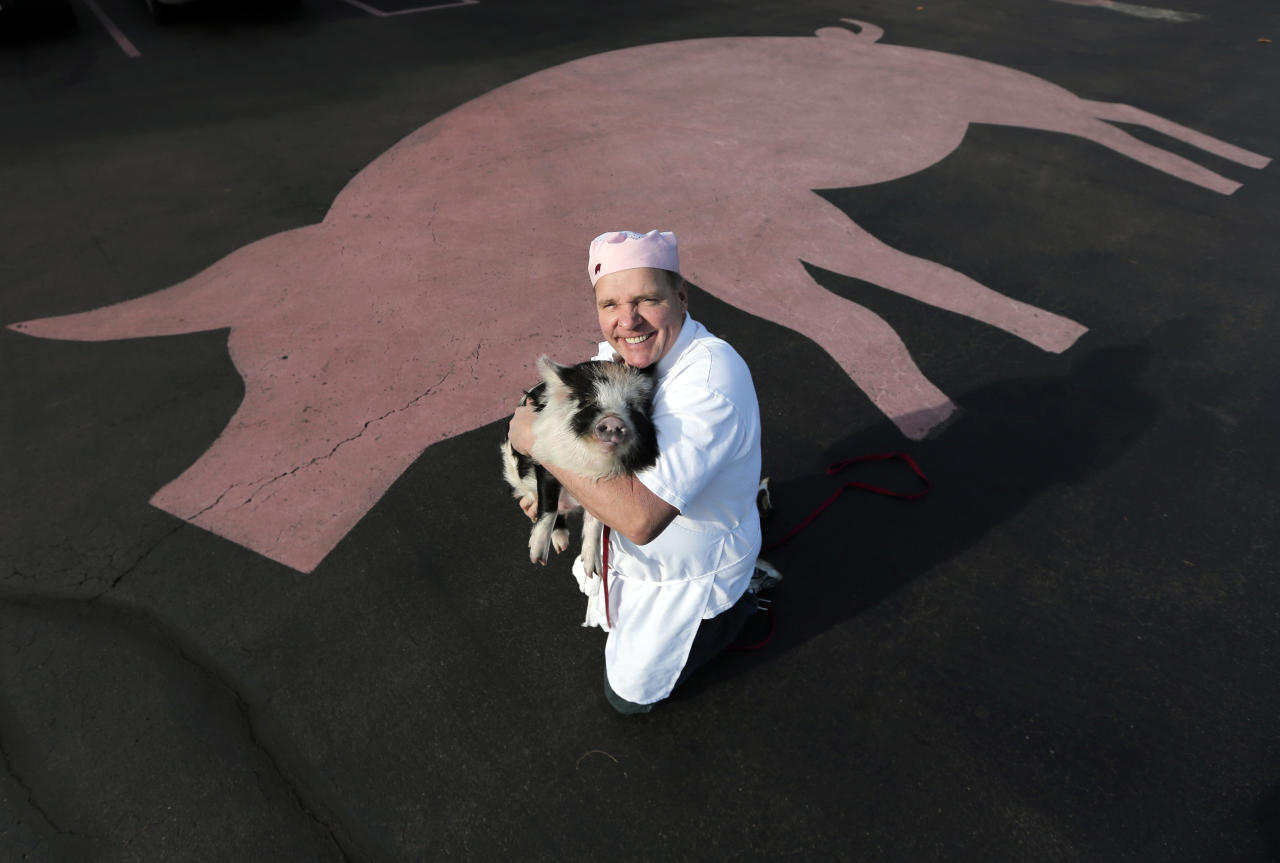 In this Dec. 6, 2012, photo, Mike Fitzgerald poses with Willie the Pig, the store mascot, in the parking lot of his Saratoga Sweets store in Halfmoon, N.Y. A holiday tradition in the upstate New York resort town of Saratoga Springs has a peppermint twist: pig-shaped hard candies are sold with little metal hammers to be smashed at Christmas. (AP Photo/Mike Groll)