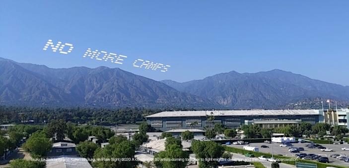 "An augmented reality visualization of the words ""No more camps"" skytyped over Santa Anita Park. The project was organized by curator Karen Ishizuka and the group Tsuru for Solidarity. <span class=""copyright"">(4th Wall AR / In Plain Sight)</span>"