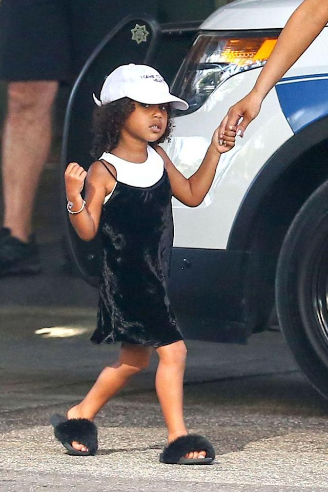 <p>North's favorite look: the slip dress. Here she rocks the crushed velvet dress over a white tank, matching perfectly with her baseball cap. She also wears the Akid Troll Aston slides, which for a time were completely sold out — could that have been because of North? (Photo: Splash) </p>