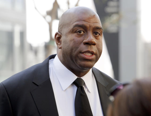 """Former Los Angeles Lakers player Earvin """"Magic"""" Johnson arrives at a memorial service for Jerry Buss, whose Lakers won 10 NBA basketball championships under his ownership, Thursday, Feb. 21, 2013 in Los Angeles. Buss died on Monday. He was 80. (AP Photo/Reed Saxon)"""