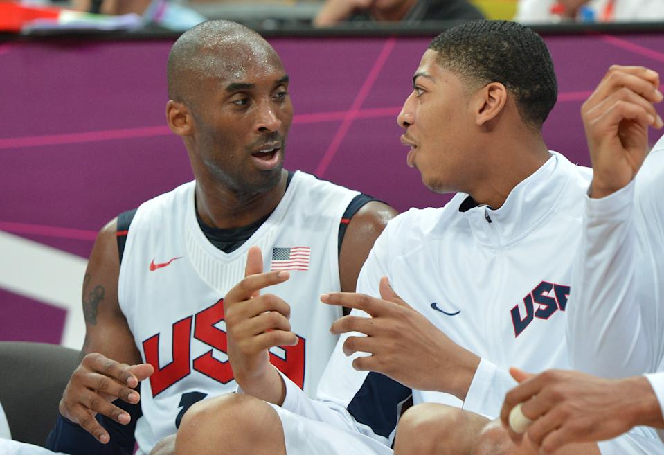 US guard Kobe Bryant (L) chats with US centre Anthony Davis (R) during the men's preliminary round basketball match USA vs Nigeria of the London 2012 Olympic Games on August 2, 2012 at the basketball arena in London. USA won 156 - 73.    AFP PHOTO / MARK RALSTON        (Photo credit should read MARK RALSTON/AFP/GettyImages)