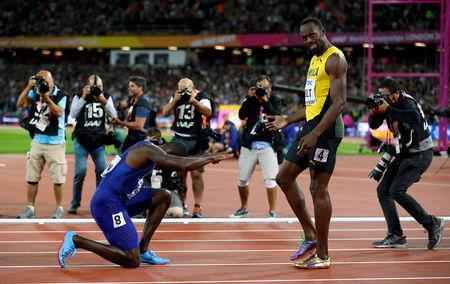 Justin Gatlin of the U.S. kneels down in front of Usain Bolt of Jamaica after the final of the Men's 100 Metres final during the World Athletics Championships at London Stadium, August 5. REUTERS/Phil Noble