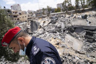 A Hamas police officer passes an crater of an airstrike that destroyed a station building prior to a cease-fire reached after an 11-day war between Gaza's Hamas rulers and Israel, in Gaza City, Saturday, May 22, 2021. (AP Photo/John Minchillo)