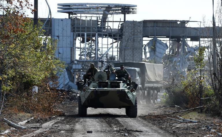 Pro-Russian armoured vehicles drive down the road leading to the remains of Lugansk International Airport, eastern Ukraine, on September 11, 2014