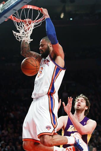 New York Knicks' Tyson Chandler (6) dunks past Los Angeles Lakers' Pau Gasol during the first half of an NBA basketball game, Friday, Feb. 10, 2012, in New York. (AP Photo/Frank Franklin II)