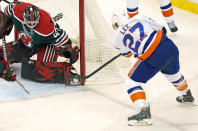 New York Islanders left wing Anders Lee (27) tries to get the puck past the pads of New Jersey Devils goaltender Aaron Dell (47) during the second period of an NHL hockey game, Tuesday, March 2, 2021, in Newark, N.J. Lee scored on the play for the Islanders winning goal. (AP Photo/Kathy Willens)