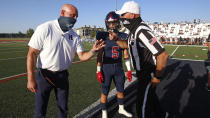 Herriman coach Dustin Pearce and Brock Hollingsworth (5) speak with an official during the coin toss before a high school football against Davis on Thursday, Aug. 13, 2020, in Herriman, Utah. Utah is among the states going forward with high school football this fall despite concerns about the ongoing COVID-19 pandemic that led other states and many college football conferences to postpone games in hopes of instead playing in the spring. (AP Photo/Rick Bowmer)