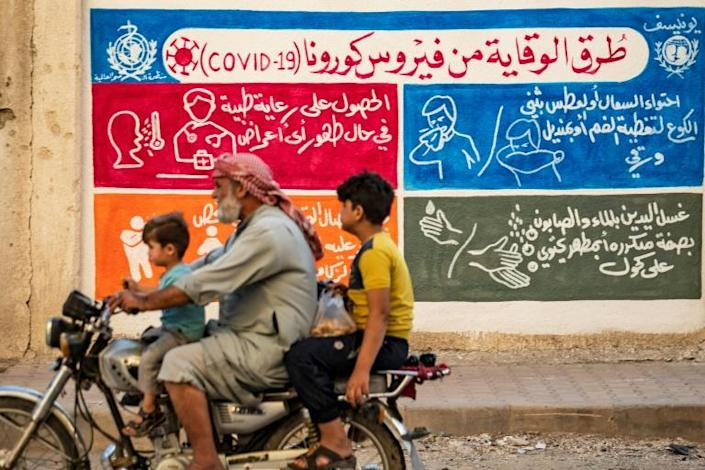 A mural in the Kurdish-majority city of Qamishli in northeastern Syria urges people to protect themselves from the virus as part of a campaign by the UN childre's fund UNICEF and the World Health Organization