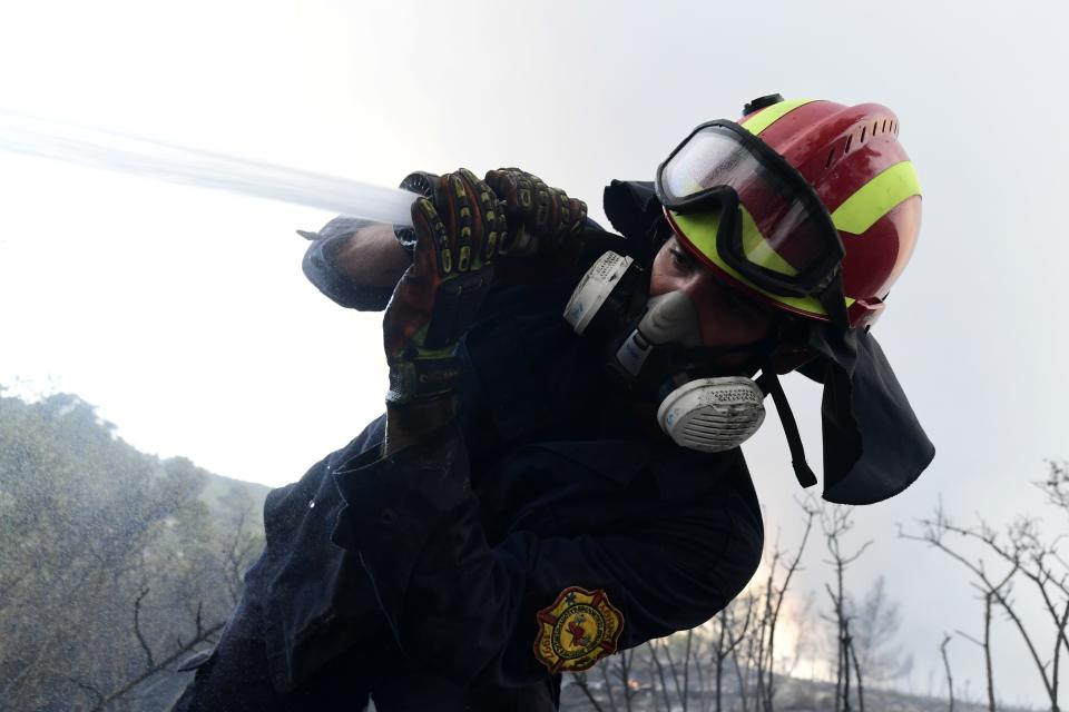 A firefighter tries to extinguish fire in Agios Stefanos, in northern Athens, Greece, Friday, Aug. 6, 2021. Thousands of people have fled wildfires burning out of control in Greece and Turkey, including a major blaze just north of the Greek capital of Athens that left one person dead. (AP Photo/Michael Varaklas)