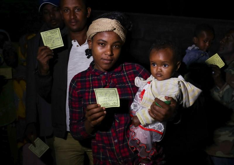 Emnet Telahun, 22, shows her voting card as she waits in a queue with her one year old daughter, Mirtinesh Mekuria, to cast her vote during the Sidama autonomy referendum in Hawassa