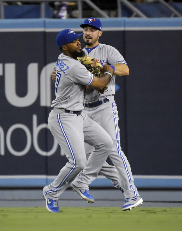 Toronto Blue Jays center fielder Teoscar Hernandez, left, and right fielder Randal Grichuk collide while trying to field a ball hit by Los Angeles Dodgers' Chris Taylor during the fourth inning of a baseball game Wednesday, Aug. 21, 2019, in Los Angeles. Taylor was thrown out at home on the play. (AP Photo/Mark J. Terrill)