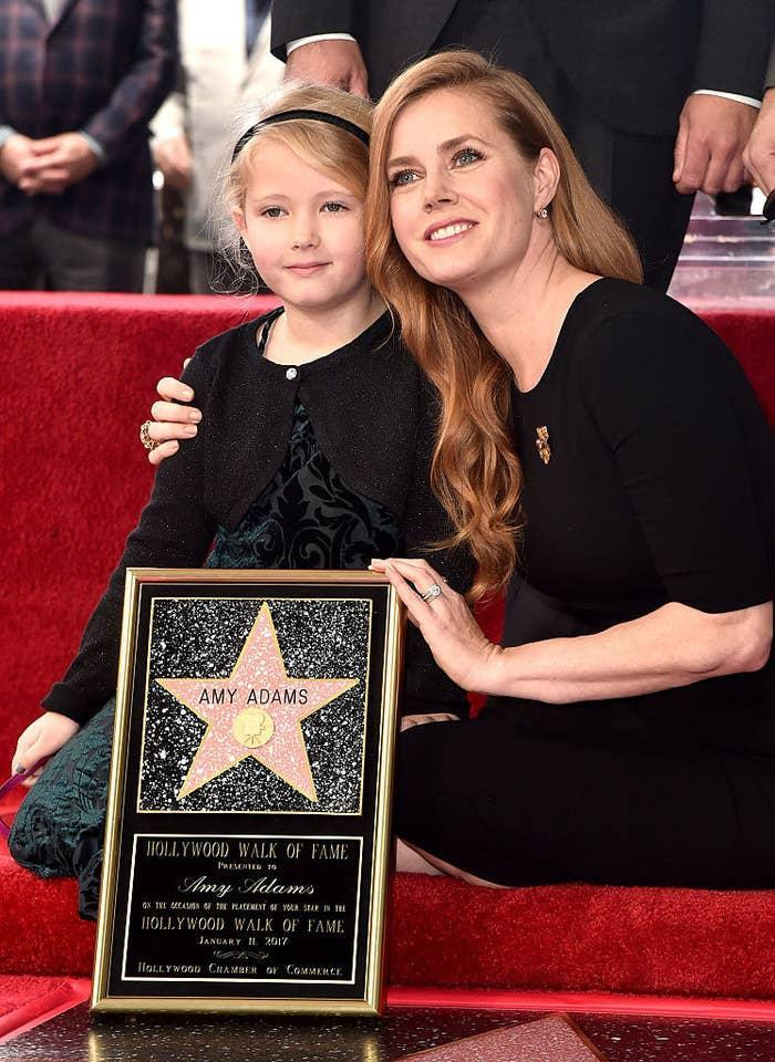 Amy Adams (R) and Aviana kneeling and posing for photos at Amy's star ceremony on the Hollywood Walk of Fame