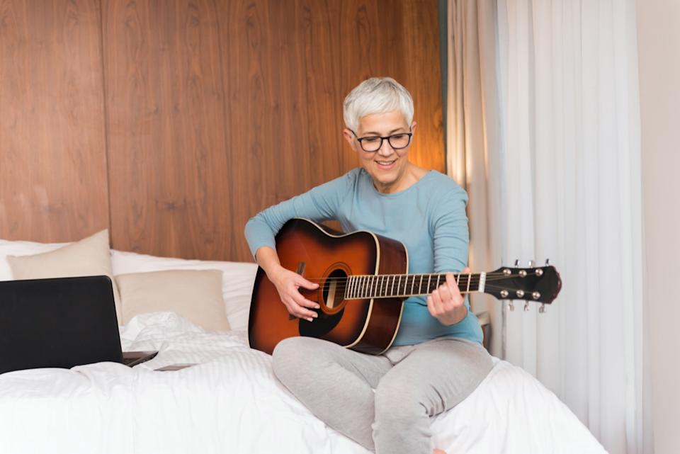 mature woman playing guitar in her bedroom, Free time and hobbies