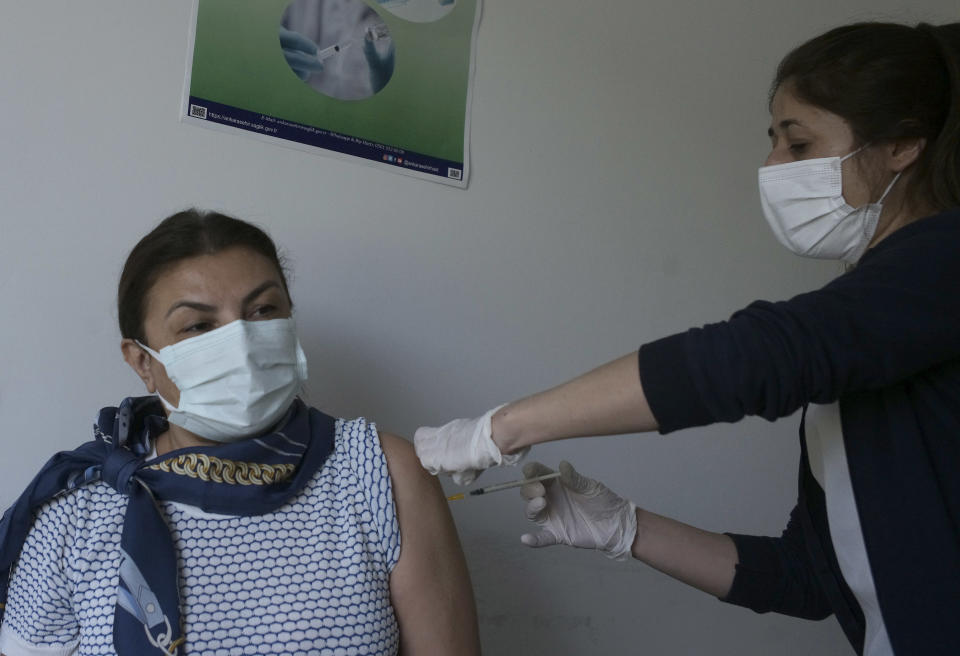 A nurse administers the second dose of Pfizer COVID-19 vaccine to a person at a hospital, in Ankara, Turkey, Saturday, May 1, 2021. Turkish President Recep Tayyip Erdogan imposed the new lockdown restrictions that will last until May 17, spanning the holy Muslim month of Ramadan and the Eid holiday, after COVID-19 infections and fatalities hit record high levels. (AP Photo/Burhan Ozbilici)