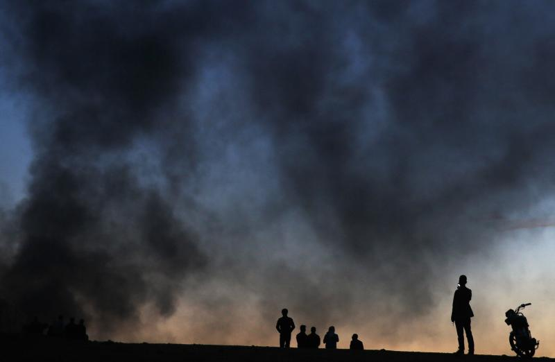 A Kurdish refugee takes photos with his mobile phone at a hilltop as thick smoke rises from the Syrian town of Kobani during heavy fighting between Islamic State and Kurdish Peshmerga forces, seen from near the Mursitpinar border crossing