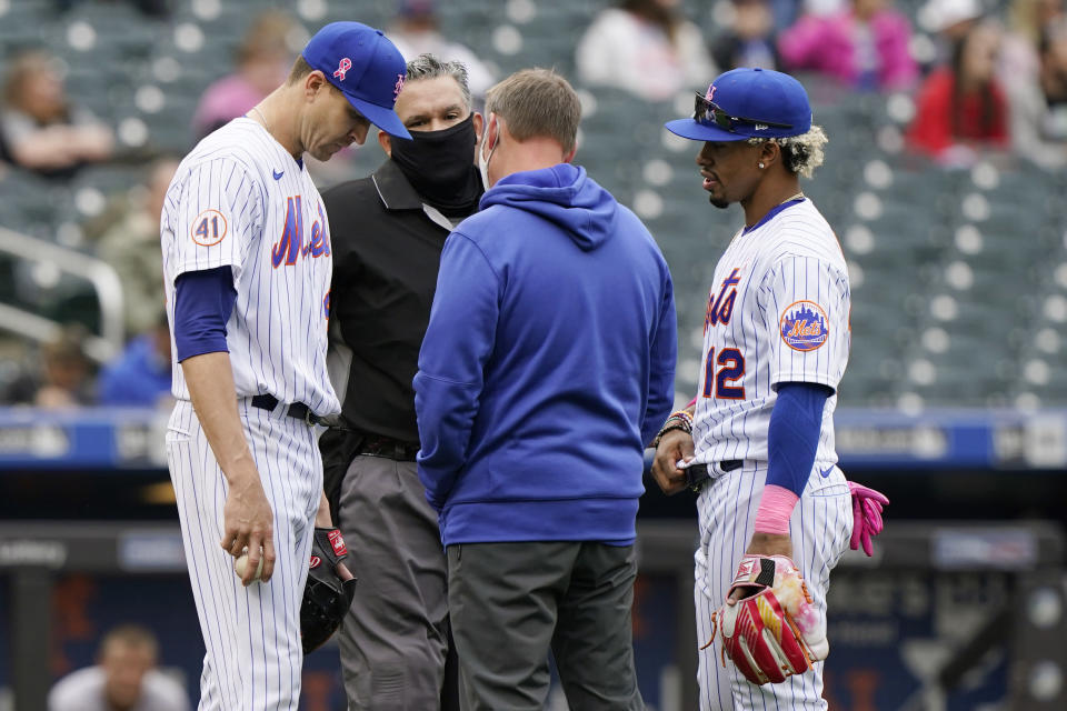 New York Mets starting pitcher Jacob deGrom, left, reacts before leaving the mound without throwing a pitch during the sixth inning of a baseball game against the Arizona Diamondbacks, Sunday, May 9, 2021, in New York. Home plate umpire Manny Gonzalez, second from left, the Mets trainer, second from right, and Mets shortstop Francisco Lindor (12) look on. (AP Photo/Kathy Willens)