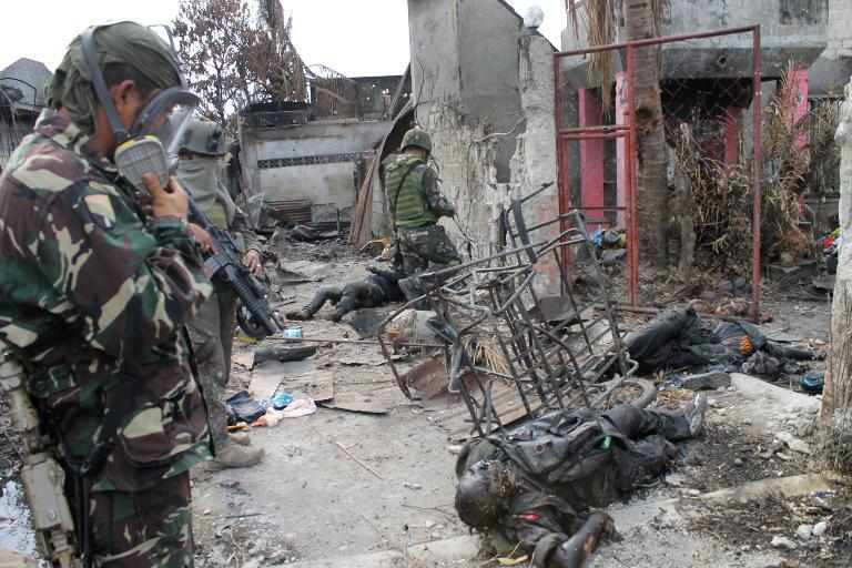 Soldiers look at bodies believed to be Muslim rebels in the Santa Catalina area of Zamboanga City on September 26, 2013
