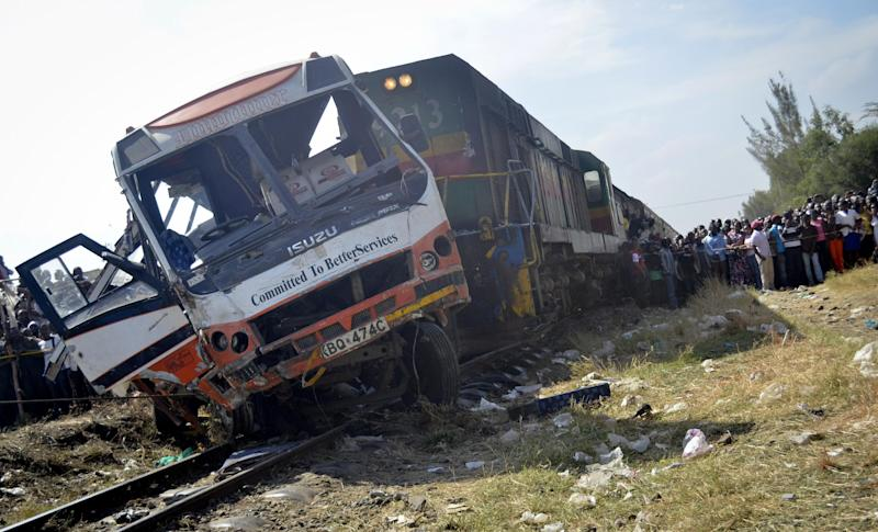 Onlookers gather around the scene of a train that crashed into a crowded bus in Nairobi, Kenya Wednesday, Oct. 30, 2013. A train crashed into a passenger bus as it passed through a rail crossing in Nairobi killing at least 11 people and injuring several others, emergency officials said. (AP Photo)