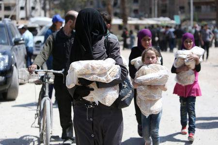 People hold stacks of bread at the city of Douma, Damascus