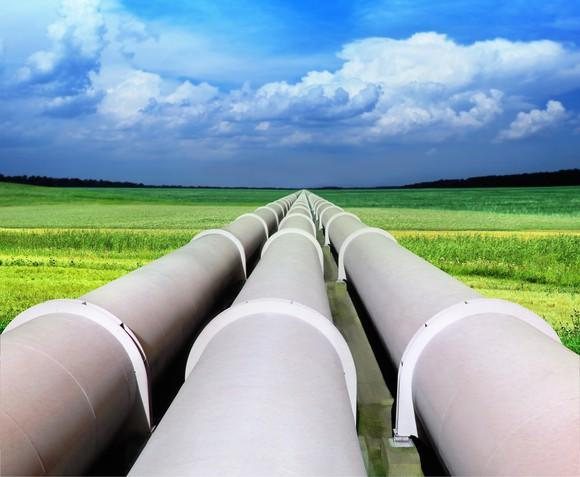 Three white pipelines in a verdant field under a cloudy sky