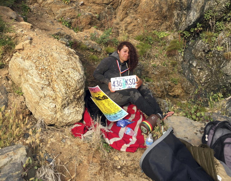 "This Friday, July 13, 2018 photo by Chad Moore shows 23-year-old Angela Hernandez of Portland, Ore., after she survived a 250-foot car plunge off a cliff and a week stranded on a remote beach near Big Sur, Calif. Moore and his wife Chelsea Moore were camping in Big Sur when they came upon a wrecked Jeep in the surf line, and then a bit later found Hernandez. ""We freakin' love that beach and we're so glad she's alive,"" Chelsea Moore said Monday, July 16, 2018. (Chad Moore via AP)"