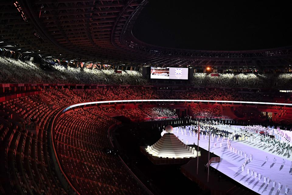 A general view shows empty seats in grandtsand as delegations enter the Olympic Stadium during the opening ceremony of the Tokyo 2020 Olympic Games, in Tokyo, on July 23, 2021. (Photo by Jeff PACHOUD / AFP) (Photo by JEFF PACHOUD/AFP via Getty Images)