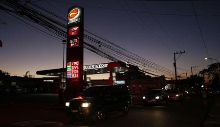 Motorists drive their vehicles past a Phoenix petrol station in Las Pinas, Metro Manila