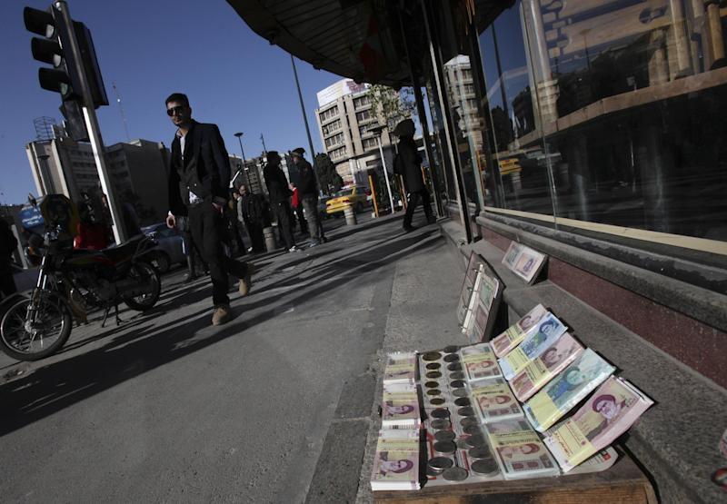 "FILE - In this Wednesday, Jan. 23, 2013 file photo, Iranian banknotes are displayed by a vendor at the side walk of the Ferdowsi Street in Tehran, Iran. Just before leaving for New York on Monday, Sept. 23, 2013, Rouhani urged Western leaders to heed his appeals for greater dialogue and take steps to ease sanctions as a way to ""reach joint interests,"" a reference to the nuclear standoff, but also possibly other regional flash points where Iran carried influence such as Iraq and Syria. (AP Photo/Vahid Salemi, File)"
