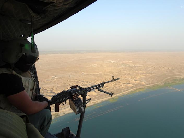 An Iraqi security forces helicopter patrols above the Euphrates river near Haditha dam September 6, 2014 (AFP Photo/Azhar Shallal)