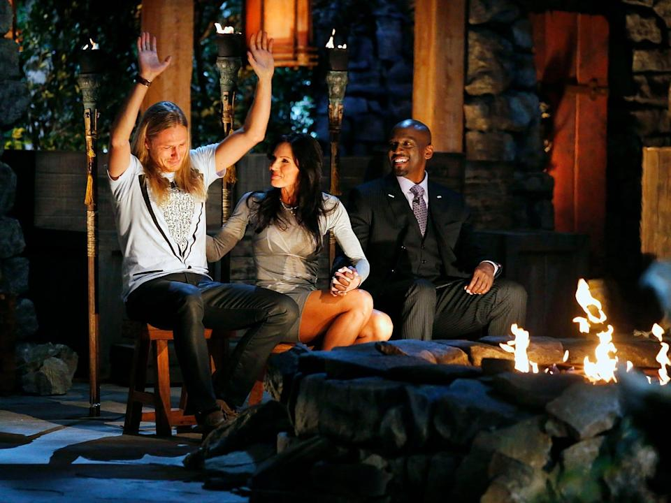 Tyson Apostol throwing his hands up after being announce the winner of his survivor season