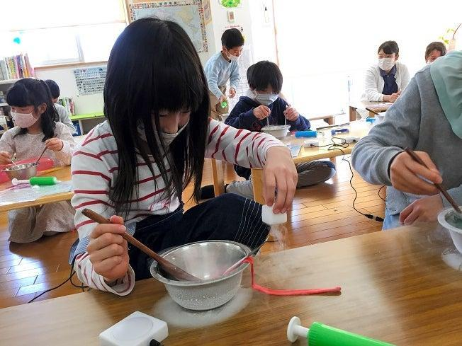 Children are involved in an experiment using liquid nitrogen at the Poppins After-School care center of Nagoya University (Poppins After-School)