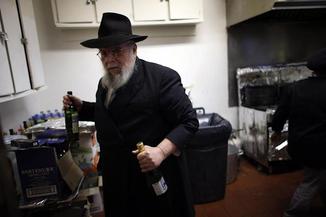 MIAMI BEACH, FL - MARCH 25: Rabbi Efraim Katz brings wine out of the kitchen for guests as he leads a community Passover Seder at Beth Israel synagogue on March 25, 2013 in Miami Beach, Florida. The community Passover Seder that served around 150 people has been held for the past 30 years and is welcome to anyone in the community that wants to commemorate the emancipation of the Israelites from slavery in ancient Egypt. (Photo by Joe Raedle/Getty Images)