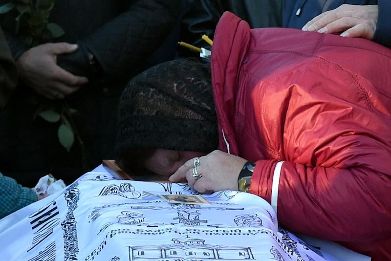 A woman grieves over the coffin of crash victim Alexei Alexeyev, 31, during his funeral at a cemetery in St. Petersburg on November 5, 2015 (AFP Photo/Vasily Maximov)