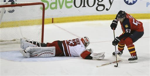 Carolina Hurricanes goalie Brian Boucher (33) is unable to block Florida Panthers' Marcel Goc (57) from scoring a goal during the first period of a NHL hockey game in Sunrise, Fla., Saturday, April 7, 2012. (AP Photo/J Pat Carter)