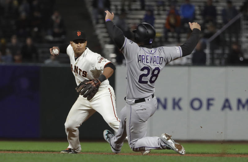 San Francisco Giants shortstop Donovan Solano, left, throws to first base after forcing out Colorado Rockies' Nolan Arenado (28) at second base during the eighth inning of a baseball game in San Francisco, Monday, June 24, 2019. The Rockies' Daniel Murphy was safe at first base. (AP Photo/Jeff Chiu)
