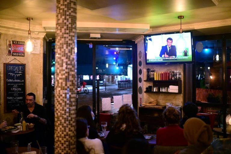 Clients at a Paris cafe watched President Emmanuel Macron's address on Wednesday, when he announced a new lockdown to combat a resurgent coronavirus outbreak.