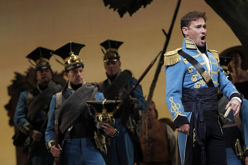"In this Sept. 20, 2012 photo, Mariusz Kwiecien performs as sergeant Belcore during the final dress rehearsal of Gaetano Donizetti's ""L'Elisir d'Amore"" at the Metropolitan Opera in New York. That most endearing of all comedies, Donizetti's ""L'Elisir d'Amore,"" opened the Metropolitan Opera season on Monday, Sept. 24 in a modest new production made memorable by an outstanding cast. (AP Photo/Mary Altaffer)"