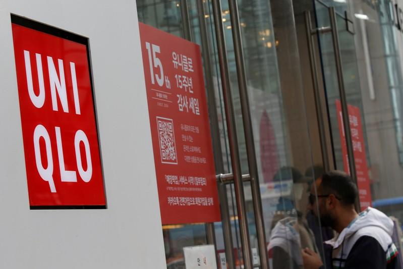 A man walks past the logo of Uniqlo at Myeongdong shopping district in Seoul